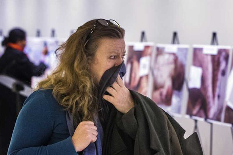 A woman reacts to images of dead bodies of Syrian detainees taken by a photographer who defected from Syria, at the UN Headquarters in New York on March 10, 2015