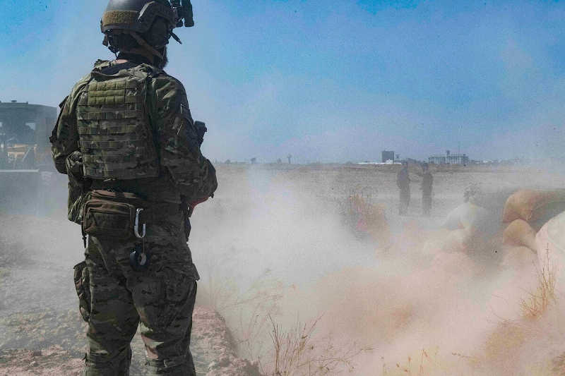 "A U.S. soldier oversees members of the Syrian Democratic Forces on Sept. 21, 2019, as they demolish a Kurdish fighters' fortification as part of the so-called ""safe zone"" near the Turkish border."