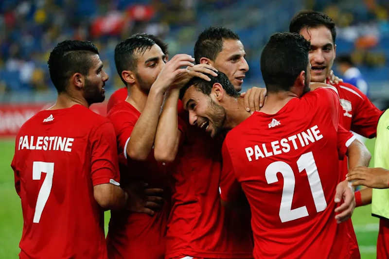The Palestinian soccer team celebrates during a FIFA World Cup qualifying match against Malaysia in June of 2015.