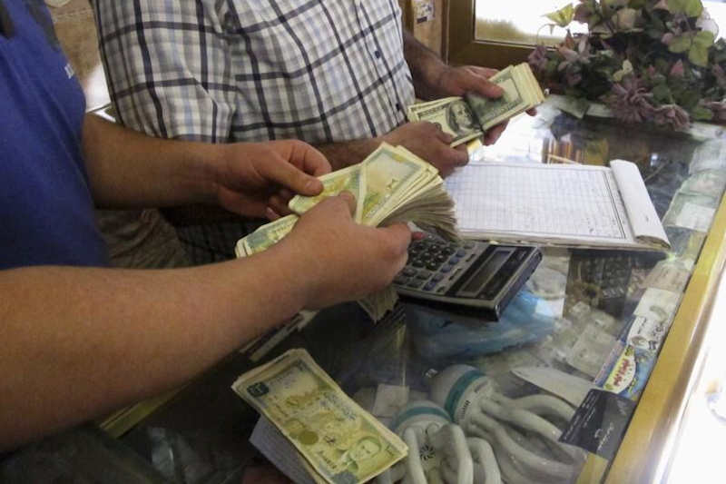 Money changers count Syrian pound notes and U.S dollars at a currency exchange shop in Aleppo's Bustan al-Qasr district, September 9, 2013.