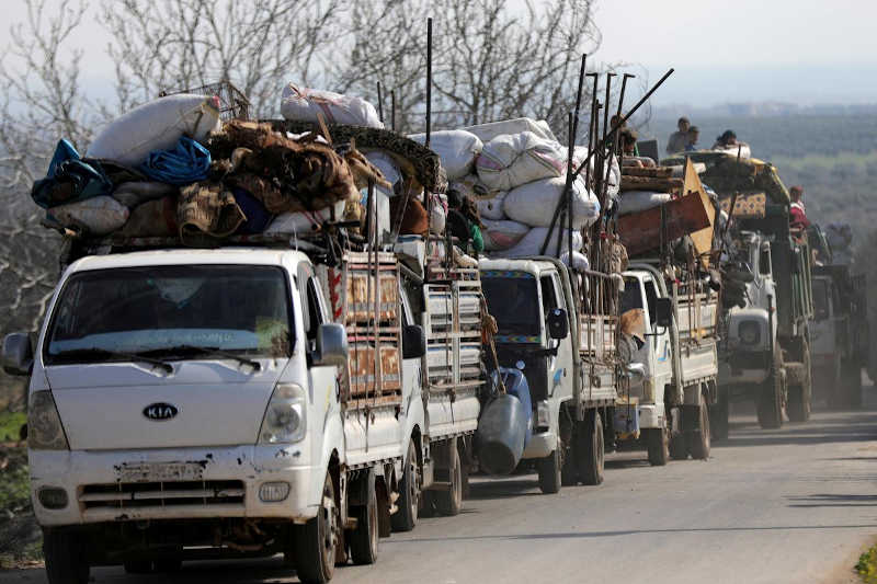 People ride on trucks with their belongings in north-east Afrin, Syria March 13, 2018.