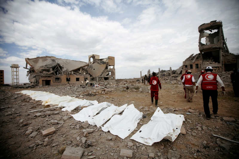 Red Crescent medics walk next to bags containing the bodies of victims of Saudi-led air strikes on a detention centre in Dhamar, Yemen.