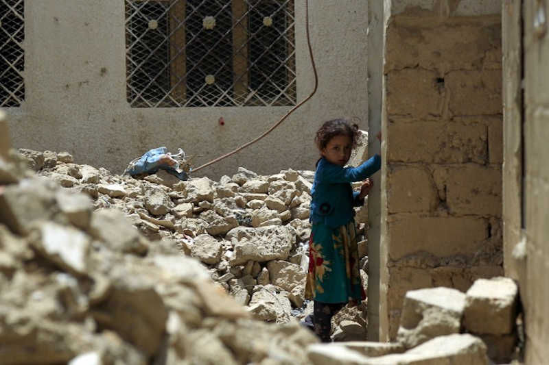 A young girl stands amidst the ruins of a building destroyed during past Saudi-led coalition air strikes, in the province of Amran, some 50 kilometres (30 miles) north of the Yemeni capital Sanaa, on July 6, 2019.