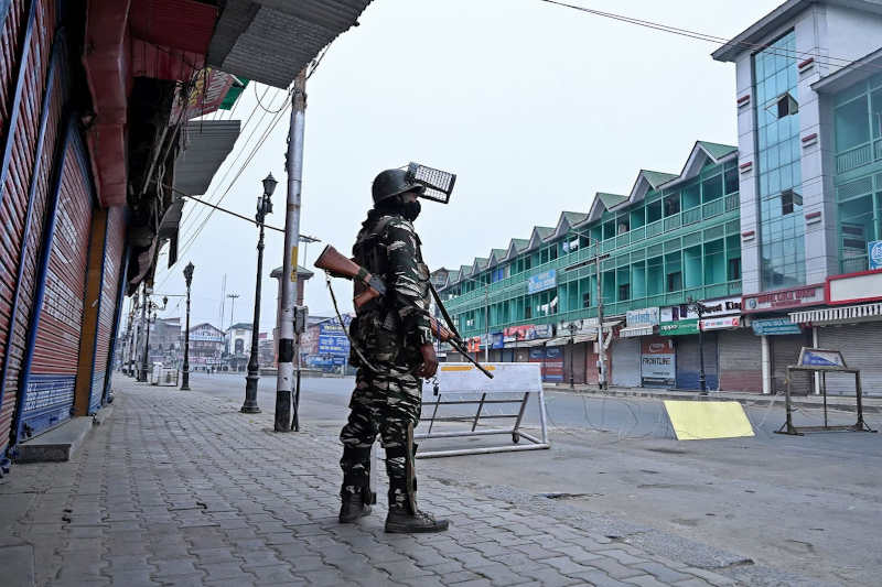 A security personnel stands guard to block a road near closed shops while strict restrictions are imposed during a lockdown in Srinagar on September 28, 2019.