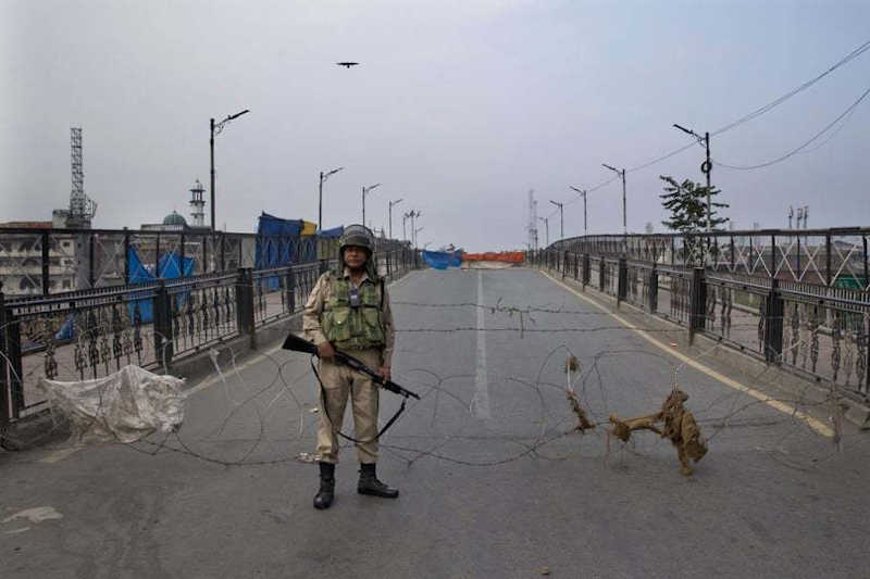 An Indian paramilitary force soldier stands guard near a barbed wire barricade during restrictions in Srinagar in occupied Kashmir on September 27.