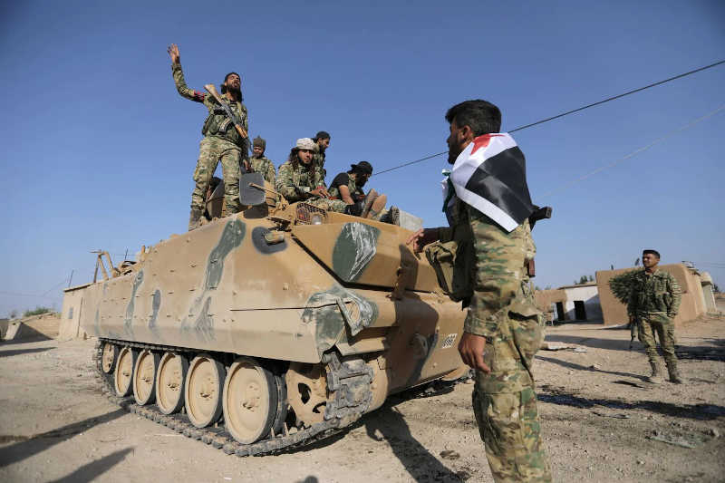 Turkish-backed fighters sit on a military truck in the Syrian village of Yabisa, near the Turkish border.