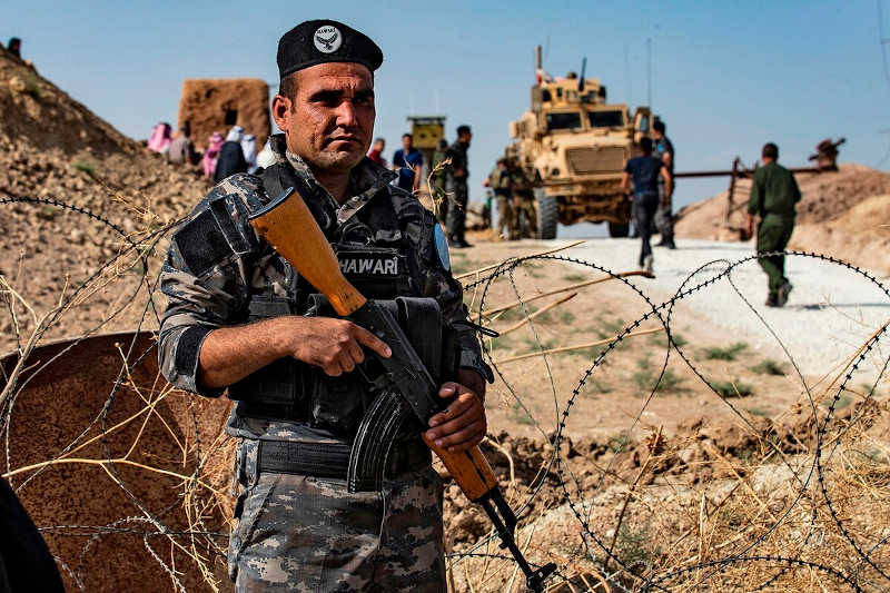 A member of Kurdish security forces stands guard during a demonstration by Syrian Kurds against Turkish threats next to a base for the U.S.-led international coalition on the outskirts of Ras al-Ain town in Syria's Hasakeh province near the Turkish border on Oct. 6, 2019.