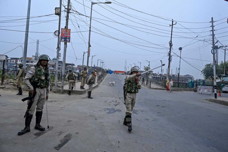 Indian security personnel gesture as they stand guard to block a road while tight restrictions are imposed as part of a lockdown in Srinagar, India-administered Kashmir, September 28. Though movement and media has been subject to controls, reports of growing unrest and human rights abuses have illicit outrage in Pakistan and beyond.